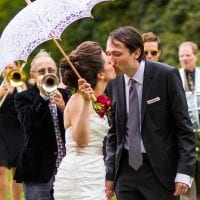 Bride and groom kissing after ceremony at cocktail with jazz band playing hot jazz music